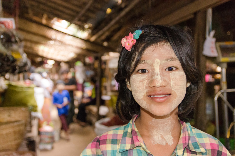 Girl in market with thanaka on her face.
