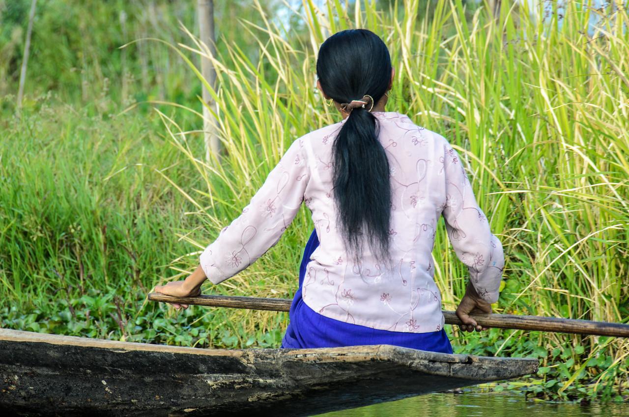 Woman rowing through floating gardens, Inle Lake.