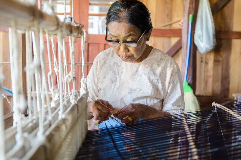 Lady weaving at a loom.