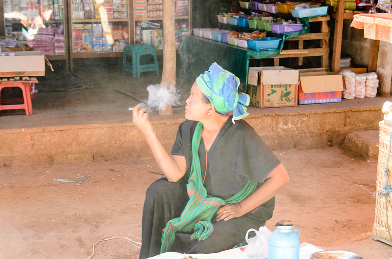 Woman smoking in the market.