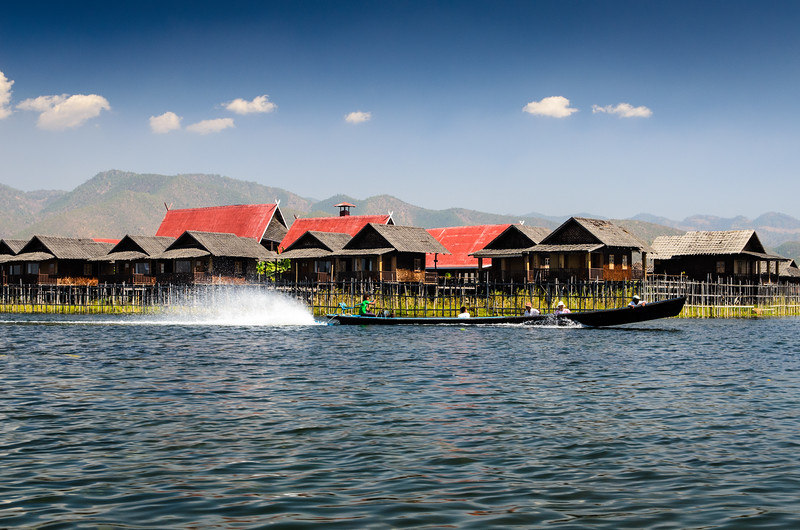 A long boat speeds by one of Inle Lakes fancy resorts.