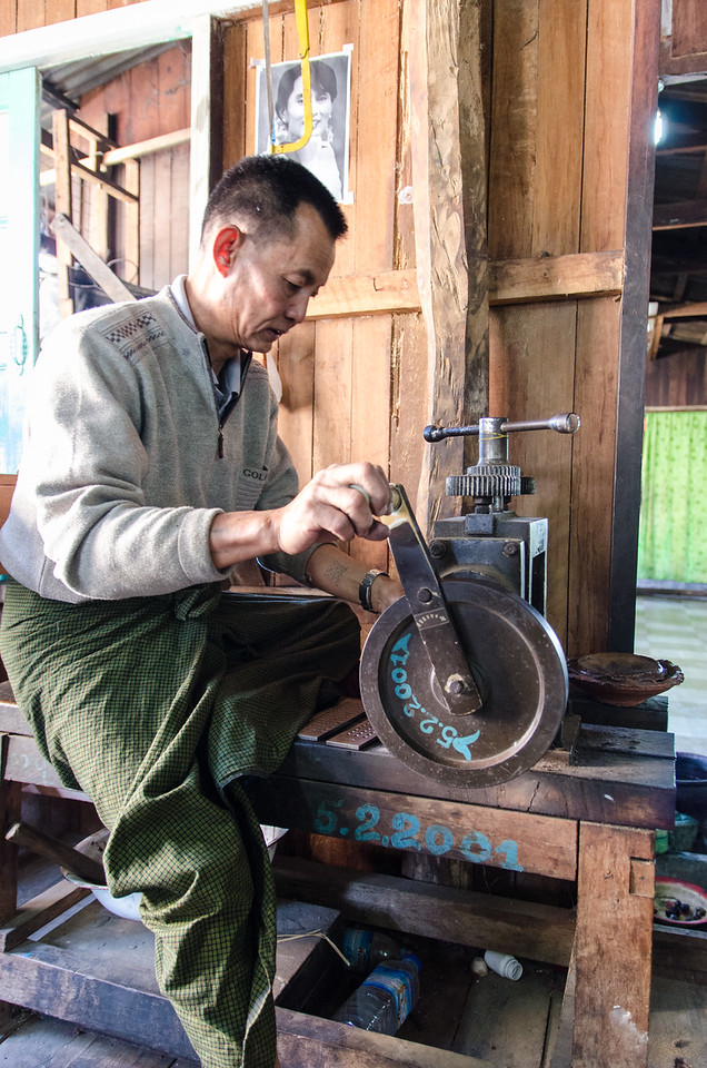 This man is using some sort of press.  I think it is part of the process to make silver chains.