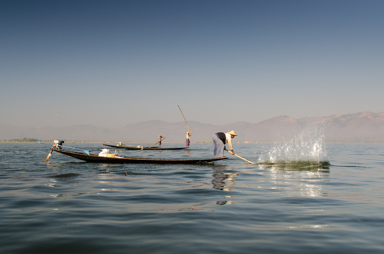 These are real fishermen.  They appear to be chasing fish into a net.