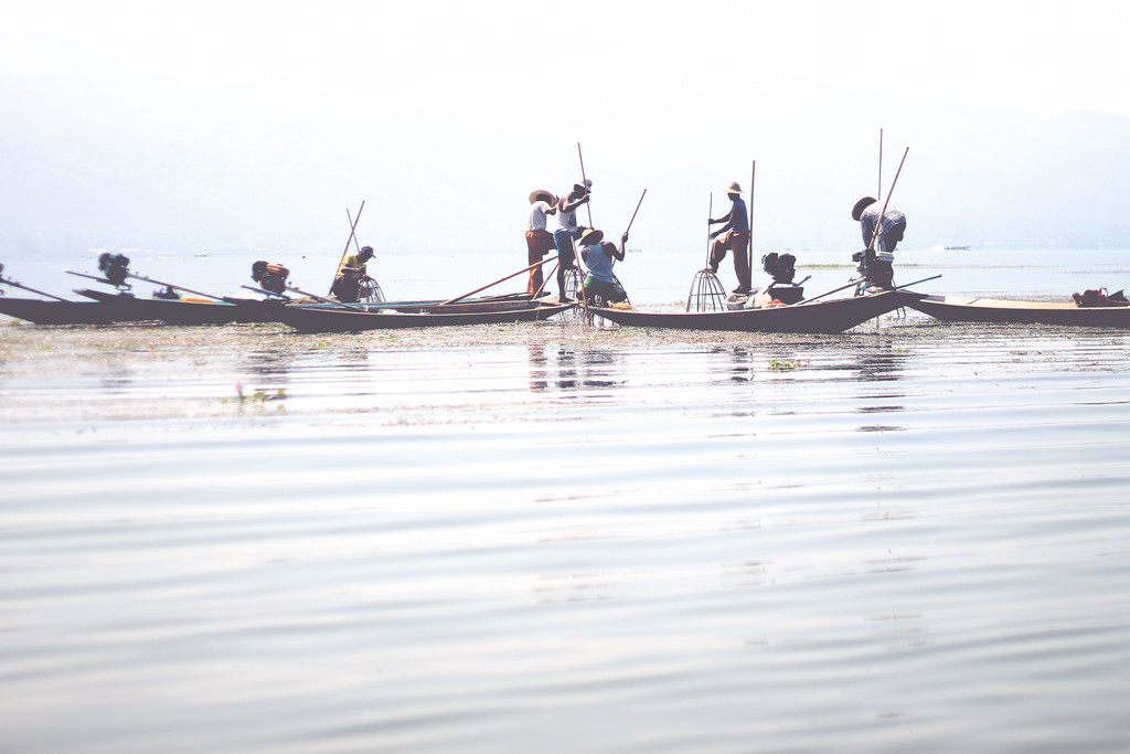 Fisherman row with one leg around the oar. The cages have nets at the bottom to trap the fish. April 2015