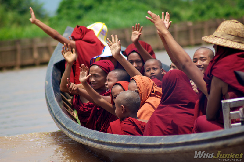 Young monks waving at us from a boat