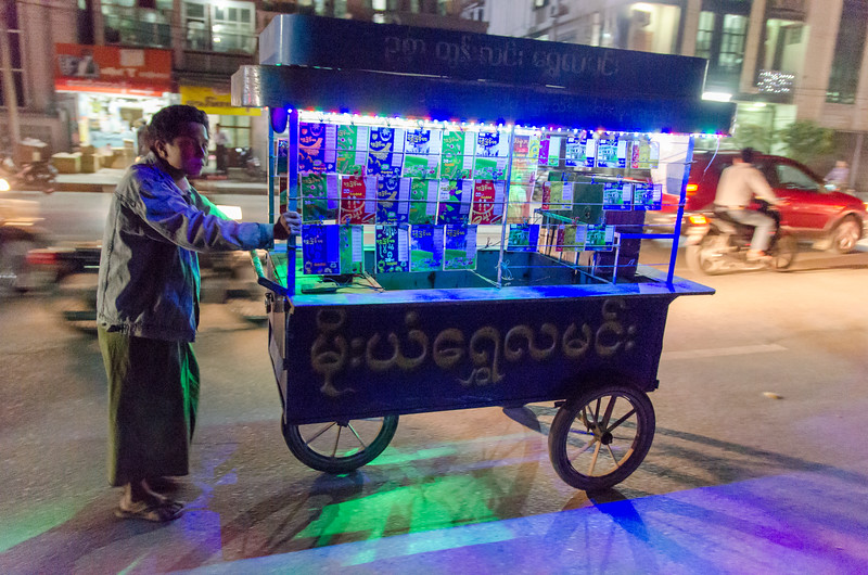 A man selling lottery tickets from a lighted cart.