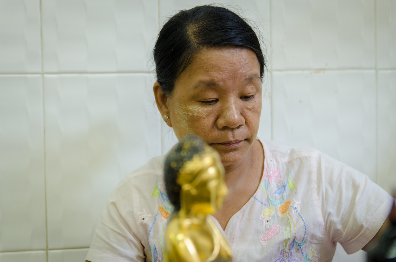 Lady applying gold leaf to a buddha statue.