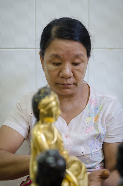 Lady applying gold leaf to a buddha statue.
