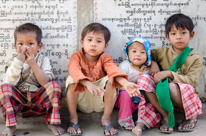 These kids were sitting on the curb an the entrance to the monastery.