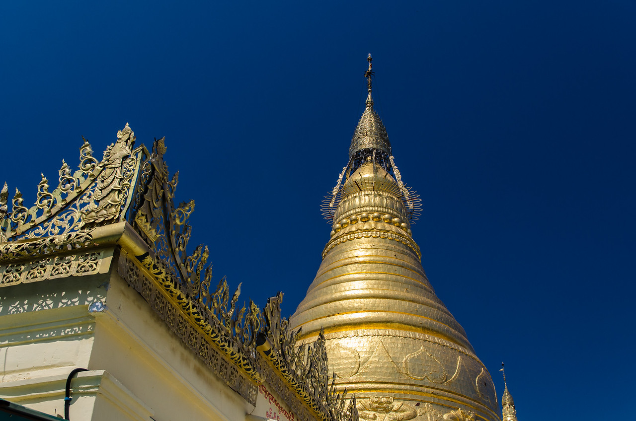Closeup of stupa with umbrella.  The umbrella is the elaborate piece at the top.