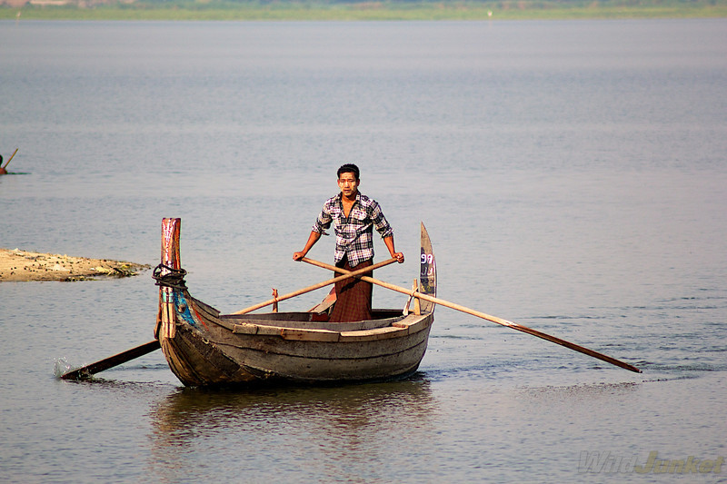 A young man rows his boat in search for tourists on the Ayeyarwady River