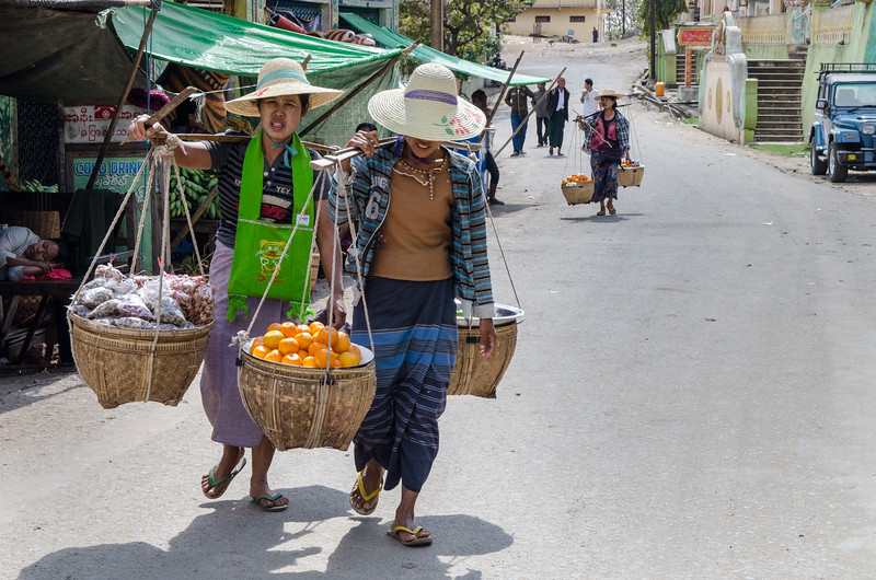 Women carrying produce at the market near the shrine.