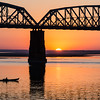 Sunset and the Inwa Bridge on the Irrawaddy with small boat.
