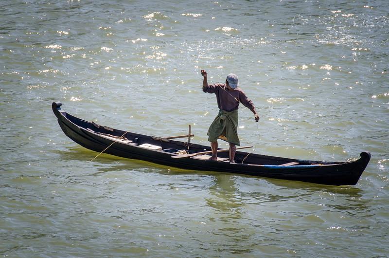 A fisherman checks his line.
