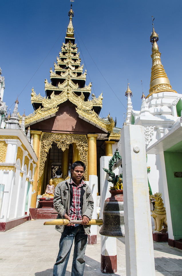 A young local fellow rings a bell at the Shwedagon Pagoda.
