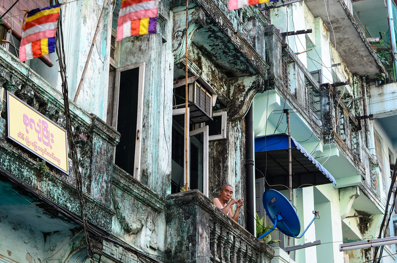 Man on balcony of old colonial Yangon apartment building.