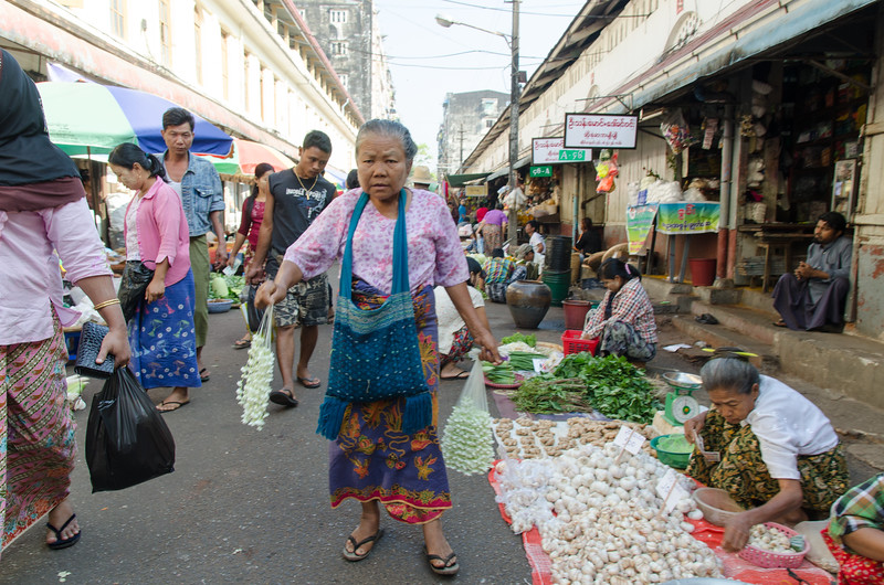 Woman selling flowers passes by other vendors.