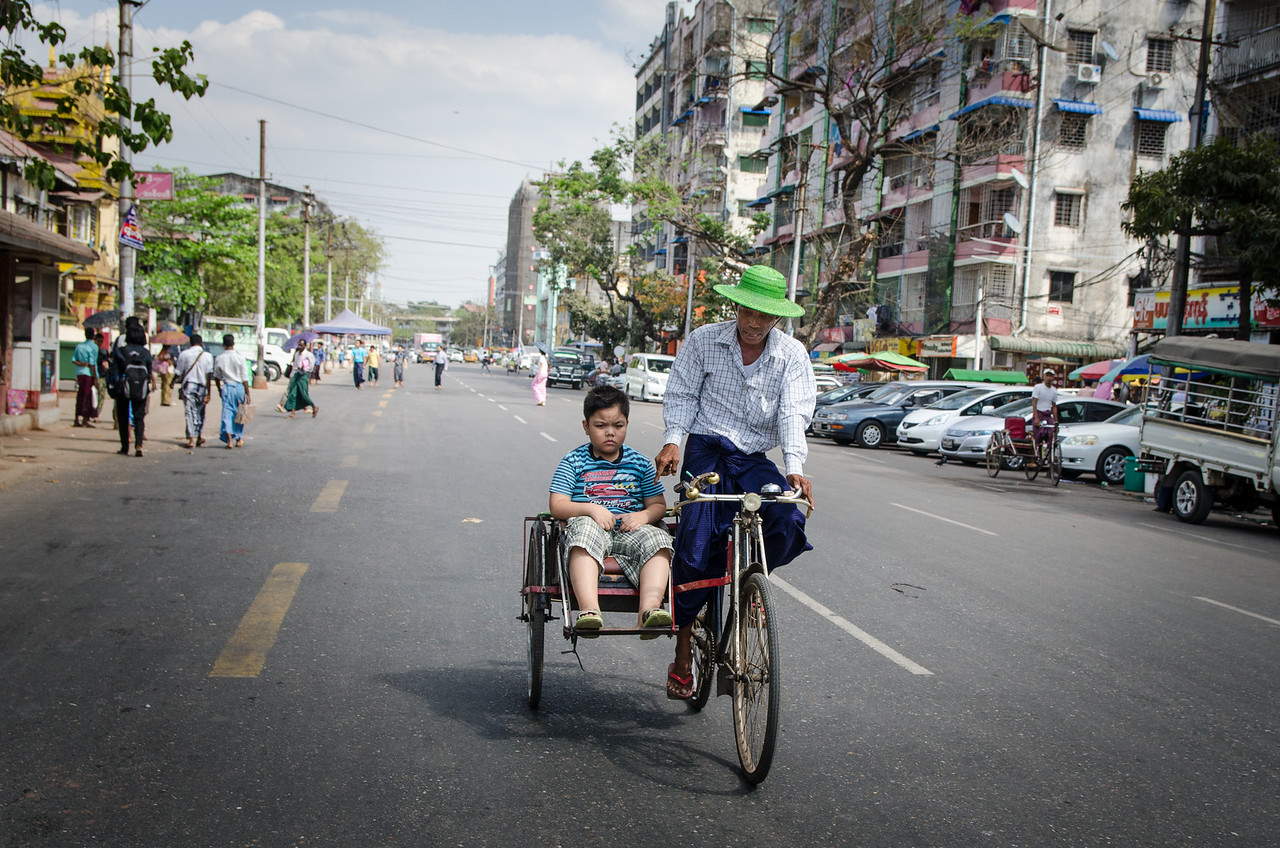 Trishaw taxi with a young passenger.