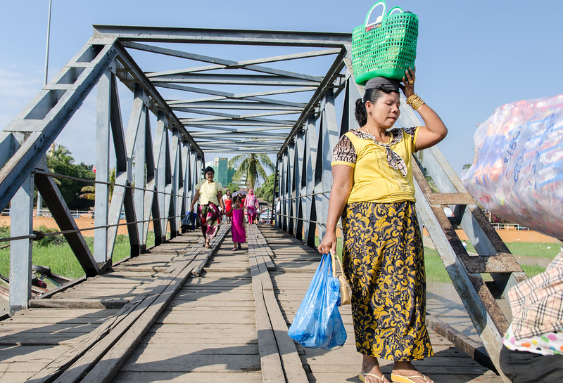 A woman crosses the bridge.