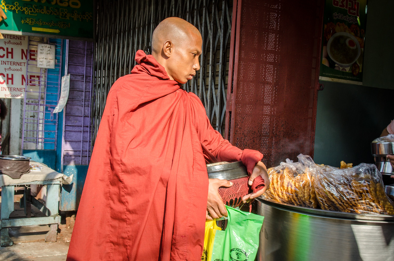A monk checking out some fried goodies.