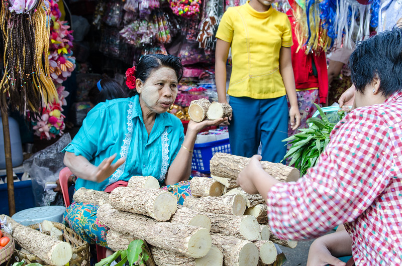 """The """"paint"""" you see on everyone's faces is ground Thanaka tree bark.  This woman is selling it."""