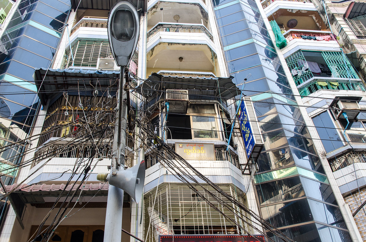 A jumble of wires in front of an apartment building.