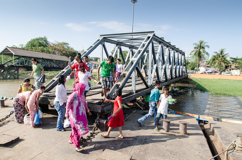 A family crossing the bridge.  People board the water taxis here to cross the Yangon River.