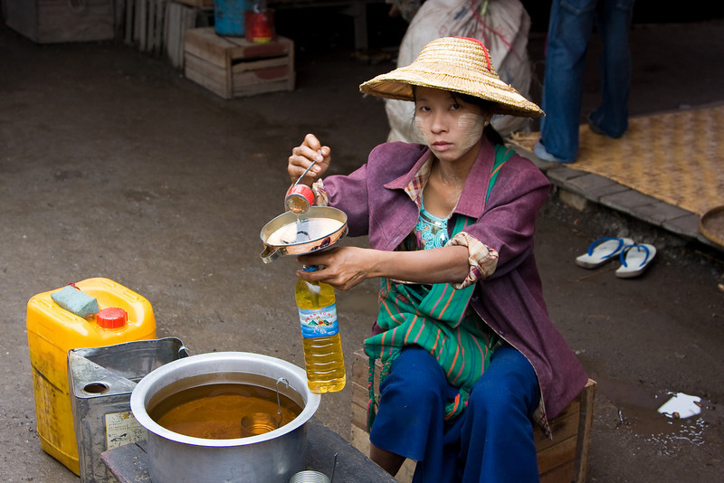 A market vendor measures out and bottles cooking oil.<br /> <br /> Location: Nyaungshwe, Myanmar<br /> <br /> Lens used: 24-105mm f4.0 IS