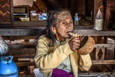 Old woman lighting a cheroot cigar