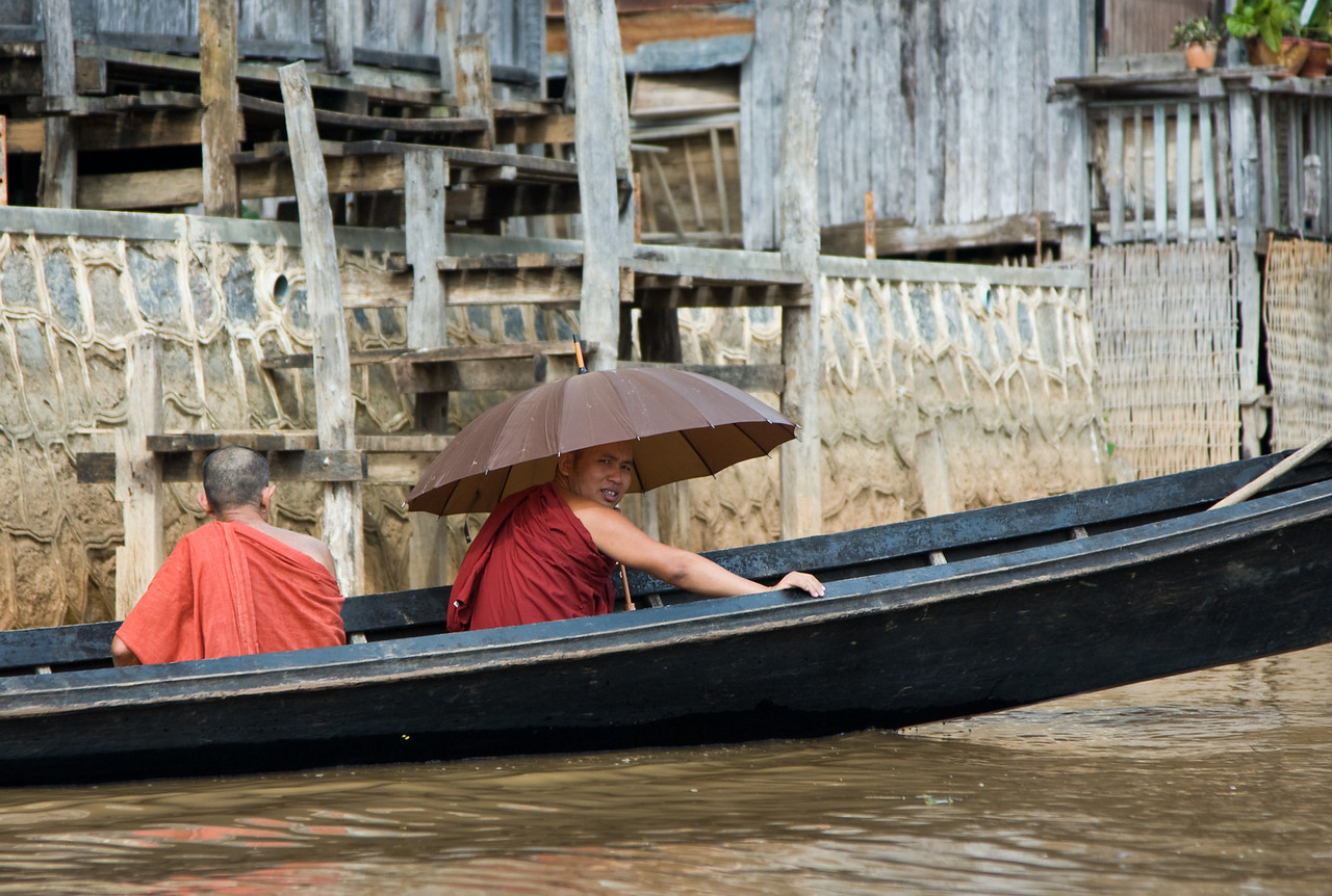 Umbrellas aren't just great for rain, they're awesome portable shade, too!  Here, a monk demonstrates.<br /> <br /> Location: Inle Lake, Myanmar<br /> <br /> Lens used: 24-105mm f4.0 IS