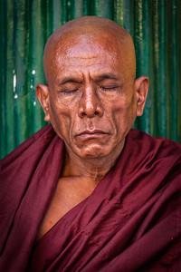 Ascetic Buddhist monk meditating in Shwedagon Paya pagoda