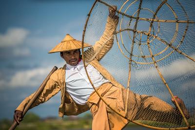 Burmese fisherman on a traditional bamboo boat using a handmade net