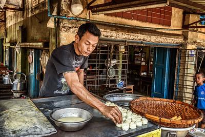 Man cooking traditional burmese street food in Yangon, Myanmar