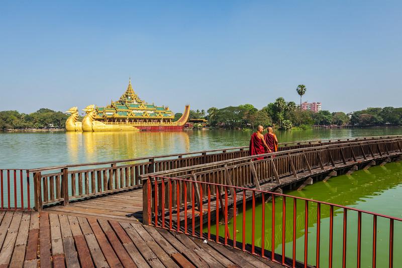 Two Buddhist monks walking on wooden bridge at at Kandawgyi Lake