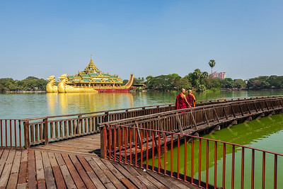 Two Buddhist monks walking on wooden bridge at at Kandawgyi Lake