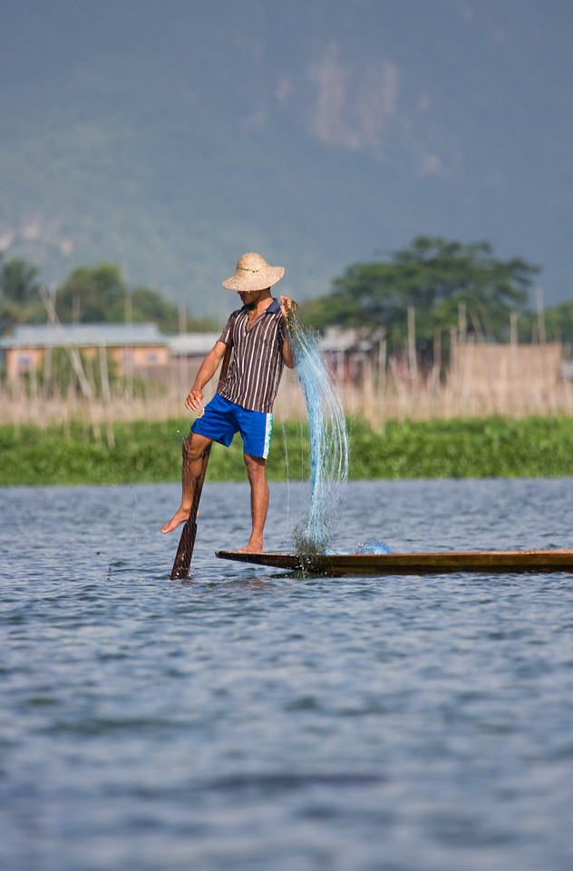 Fisherman pulling his net.<br /> <br /> Note that he's rowing his boat without using his hands.  Very 'handy'!<br /> <br /> Location: Inle Lake, Myanmar<br /> <br /> Lens used: 100-400mm f4.5-5.6 IS