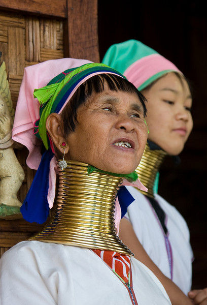 From what I understand, there are tribes in this region of Asia that still practice the tradition of elongating the necks of their women with these disks.  In Myanmar, from what I was told, they live 'in the south'.<br /> <br /> Because I photographed these two women at a tourist craft shop, there is the question of their authenticity.   The disks they wore, however didn't appear to be of the removable-at-the-end-of-the-work-day variety, so my guess is they're the real deal.  Perhaps these women relocated from their remote villages to the much more touristy Inle lake region to try to increase their income-generating opportunities.<br /> <br /> Location: Inle Lake, Myanmar<br /> <br /> Lens used: 24-105mm f4.0 IS