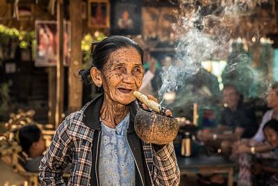 Old wrinkled woman smoking  a big cheroot cigar