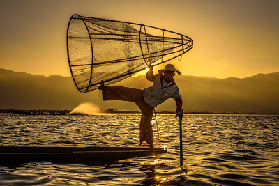 Burmese fisherman on a bamboo boat at sunrise