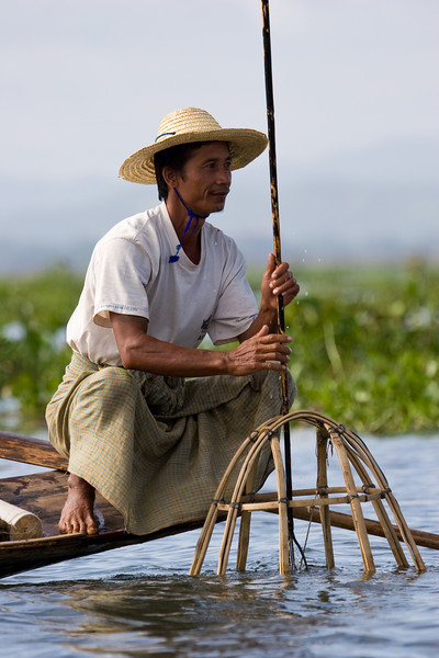 Fisherman 'churning' the water to suck fish into his bamboo net.<br /> <br /> Location: Inle Lake, Myanmar<br /> <br /> Lens used: 100-400mm f4.5-5.6 IS