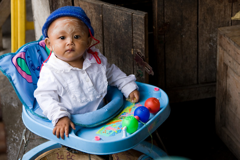 Cute kid in his walker behind the counter at the town market.<br /> <br /> Location: Nyaungshwe, Myanmar<br /> <br /> Lens used: 24-105mm f4.0 IS