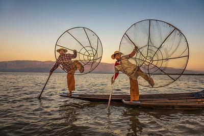 Burmese fishermen on bamboo boats at sunrise