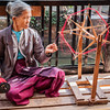 Burmese woman spinning yarn at weaving factory