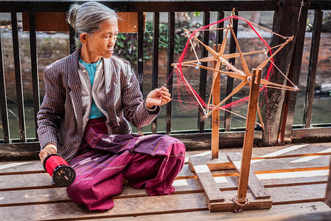 Burmese woman spinning yarn at weaving factory