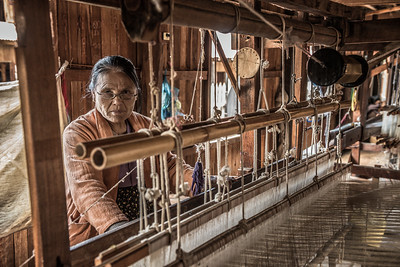 Woman worker weaves fabric in a weaving factory