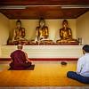 YANGON, MYANMAR - JANUARY 3, 2014: Man and Buddhist mokn meditating and worshipping statues of Buddha in Shwedagon Paya pagoda