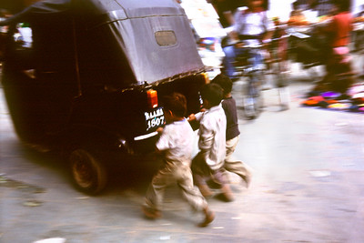 Kids running behind a Tuk Tuk