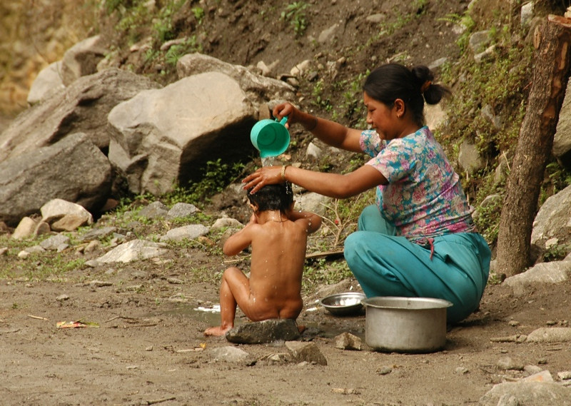 Mother Giving Child A Bath - Annapurna Circuit, Nepal