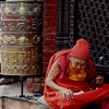 An old Buddhist monk in Bodhnath praying next to a prayer wheel which was just spun by a passing devotee.