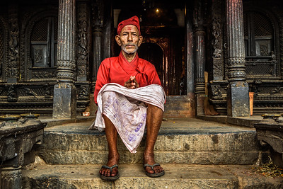 Old buddhist monk sitting in front of his temple in Kathmandu